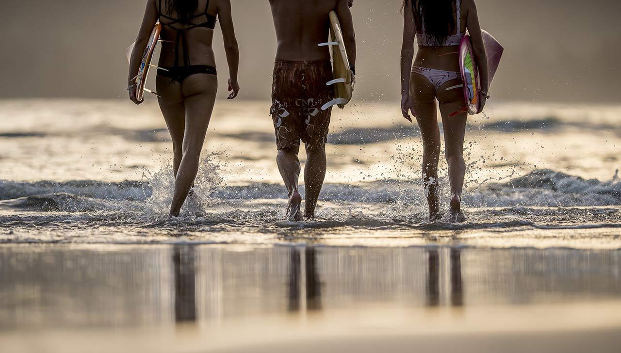 Marche sur la plage de trois surfeurs